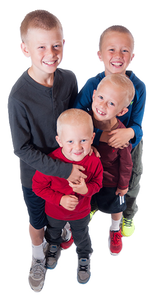 A group of four boys hugging and smiling