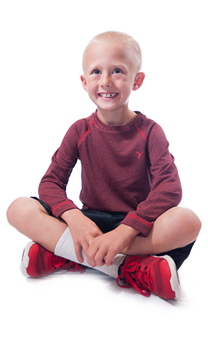 Smiling young boy sitting cross-legged