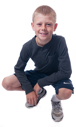 A smiling young man sitting in a crouch