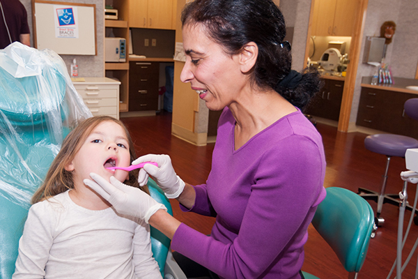 Dr. Fariba showing a young patient how to brush her teeth at Great Grins for KIDS - Oregon City