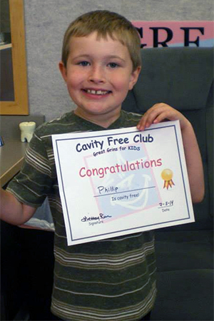 A happy, cavity-free patient holding up his Cavity Free Club certificate