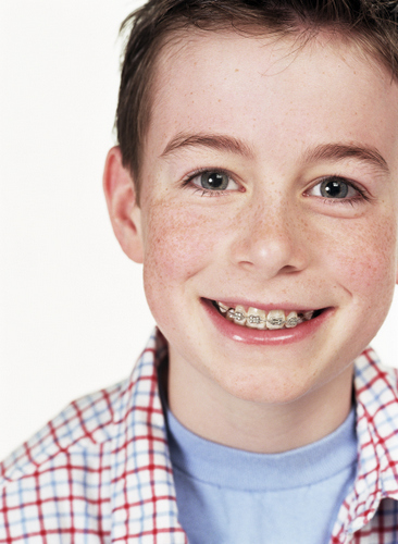 A young boy with braces on his teeth.