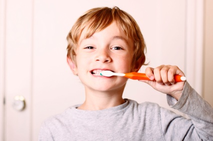 A young boy brushing his teeth; and trying to swallow toothpaste.
