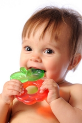 A young baby chewing on a teething ring.